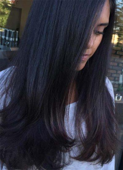 chica joven con cabello largo y negro con un corte en capas en los extremos