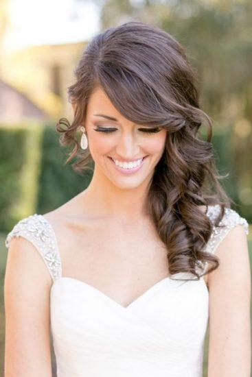 Chica con cabello largo vestida de novia y peinada con ondas grandes y un semi-recogido