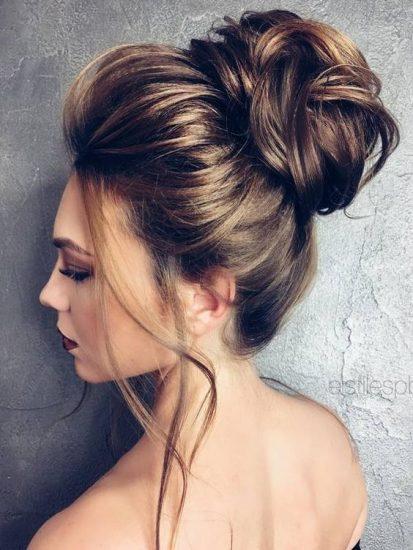 Una novia con un peinado con recogido alto y mechas sueltas.