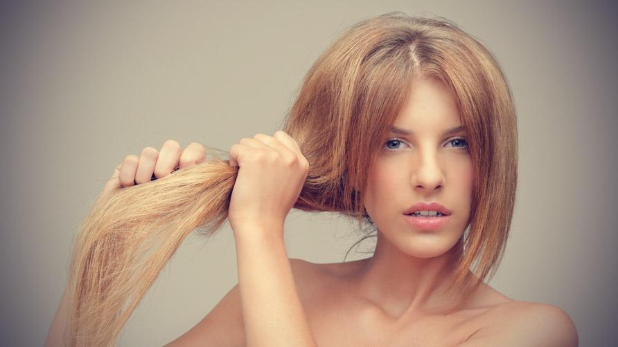 Mujer rubia estirando su cabello reseco