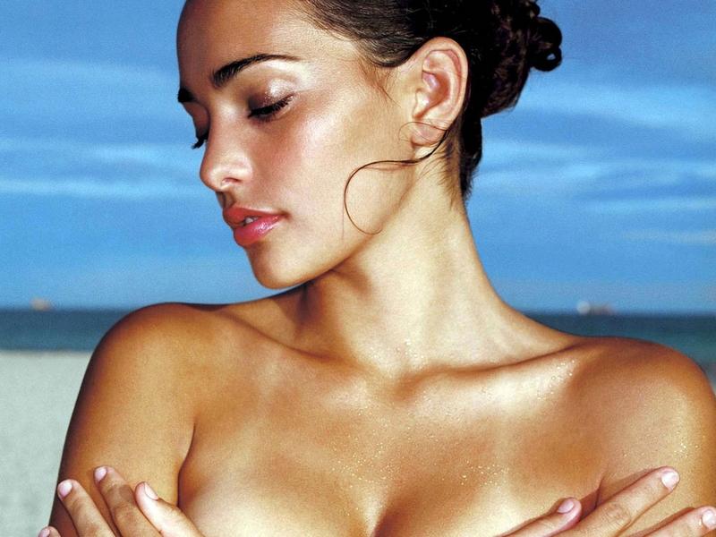 Mujer que lleva la piel morena por usa autobronceadores