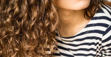 chica con cabello ondulado por el uso de mascarillas caseras