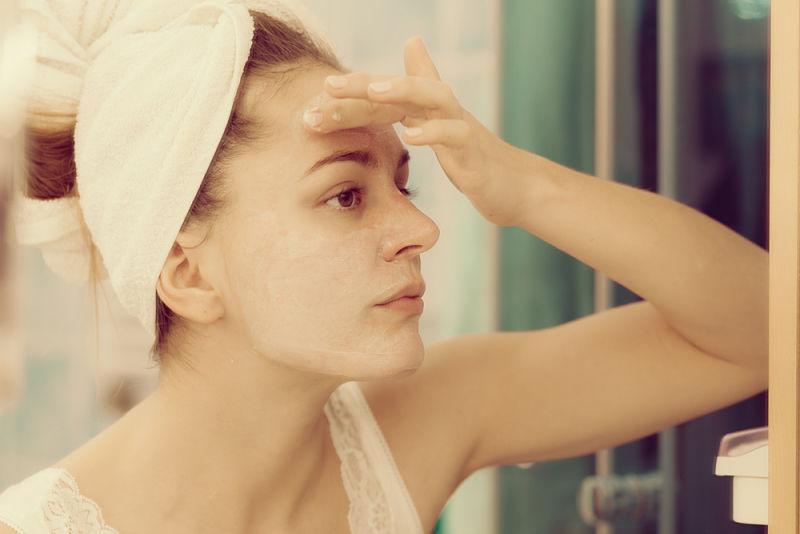 mujer joven aplicando crema por un problema de resequedad en la piel
