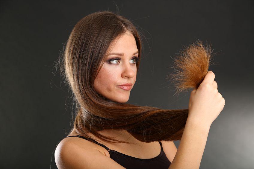 Chica mirando su cabello con puntas abiertas antes de aplicar una crema para tratarlo