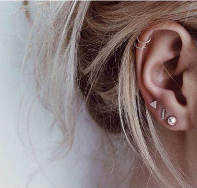 Chica rubia con perforaciones en la oreja