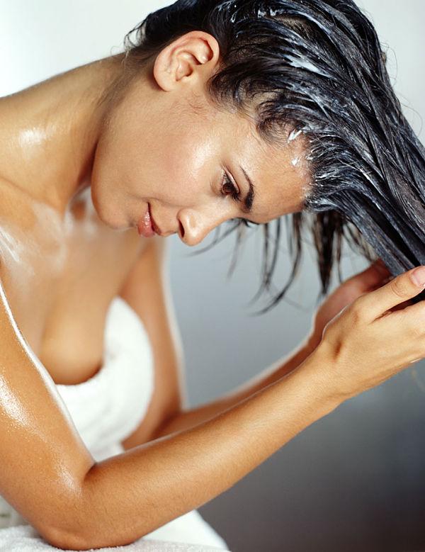 Una chica aplicando una mascarilla casera en su cabello para poder alisarlo