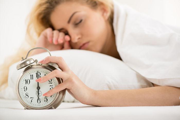 Mujer joven soñolienta en su cama apagando la alarma de su reloj para levantarse por las mañanas