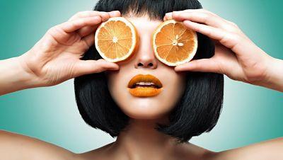 mujer sosteniendo naranjas que son buenas para ayudar a la piel a protegerse de los rayos solares