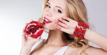 mujer con granada saludable en una mano como parte de una dieta antiedad