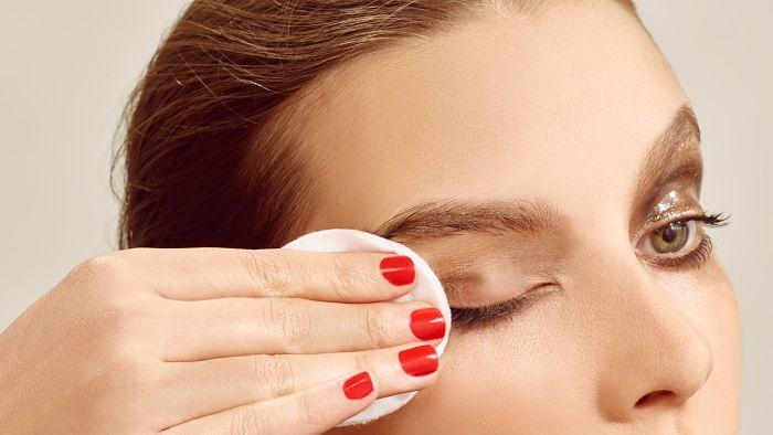 mujer removiendo maquillaje para tener una piel limpia de sus ojos