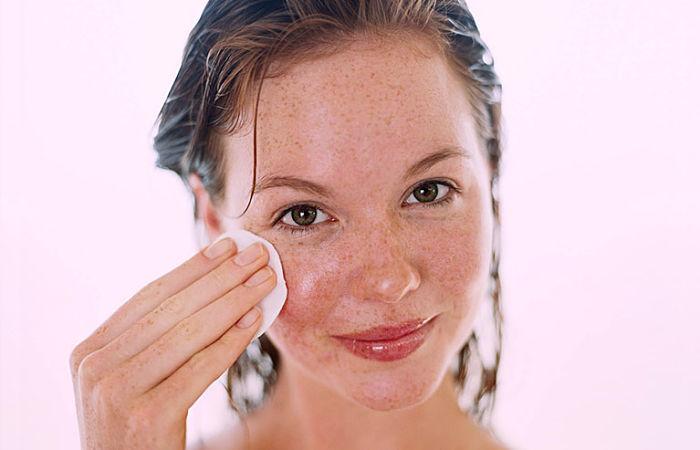 mujer limpiando su rostro con piel grasosa