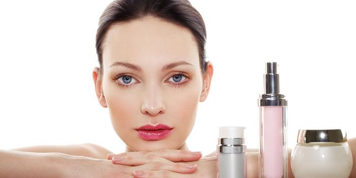 mujer con varios productos dermocosméticos y cosméticos
