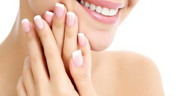 mujer joven enseñando uñas bonitas y saludables