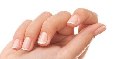 Mano de mujer con uñas saludables y brillantes sobre fondo blanco, lo que tus uñas dicen sobre tu salud