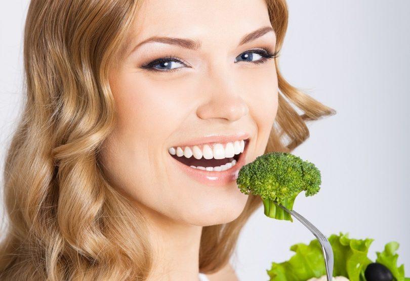 Mujer joven rubia comiendo brócoli que es uno de los mejores alimentos para cuidar tu piel