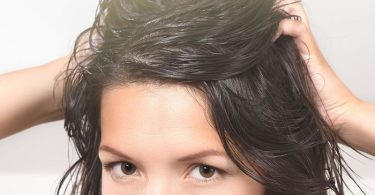 Mujer joven con manos en la cabeza y cabello graso