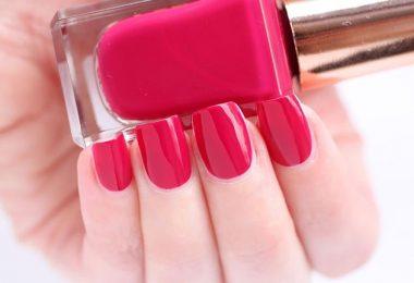 Mano de mujer con uñas pintadas sosteniendo un frasco de esmalte