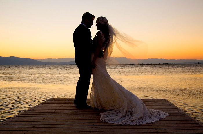 Pareja de novios casándose en la playa al atardecer. Dónde es mejor hacer tu boda