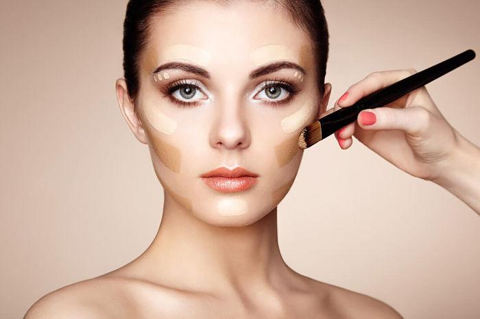 Mujer joven aplicando base de maquillaje en su rostro, para elegir el tono de base de maquillaje