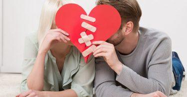 Pareja joven sosteniéndo un corazón roto arreglado para salvar su relación