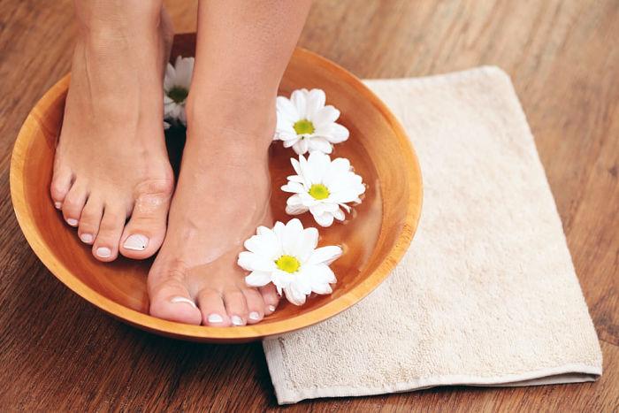 Pies de mujer sumergidos en agua especial para tratamiento de los pies