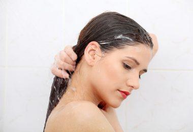 Mujer joven lavando su cabello en la ducha. Lavart tu cabello sin champu.
