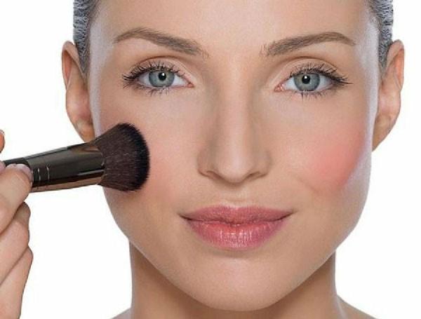 Mujer aplicando iluminador para lucir maquillaje