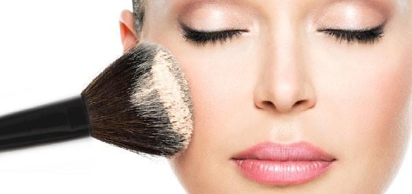 Mujer aplicando polvo a su rostro para lucir el maquillaje