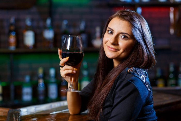 Mujer en bar usando maquillaje de noche