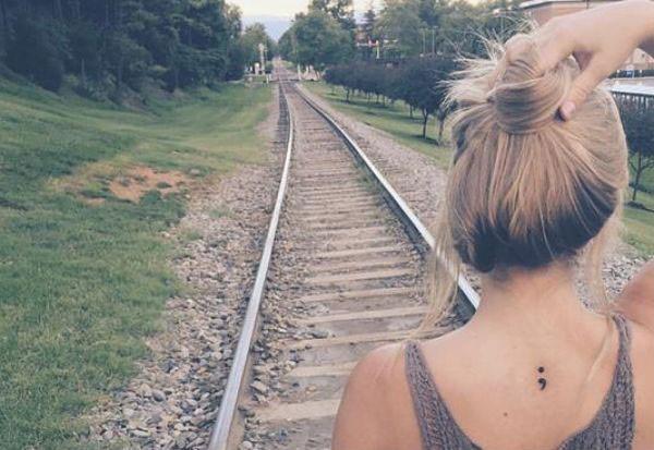 Tatuaje de punto y coma en la espalda