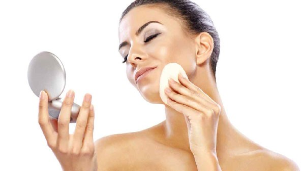 Mujer aplicando base de maquillaje