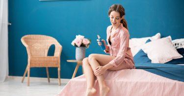 Mujer hidratando la piel de sus piernas