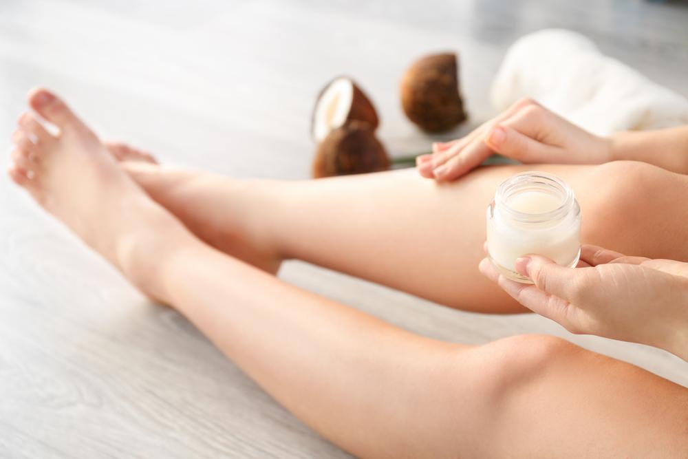 Mujer aplicándose aceite de coco en las piernas