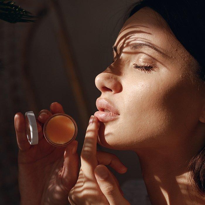Mujer aplicándose bálsamo de labios con cera de abejas y coco