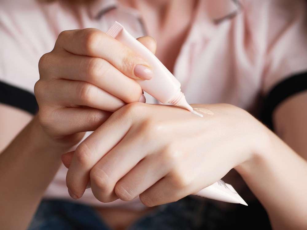Mujer se está aplicando base de maquillaje sobre su mano