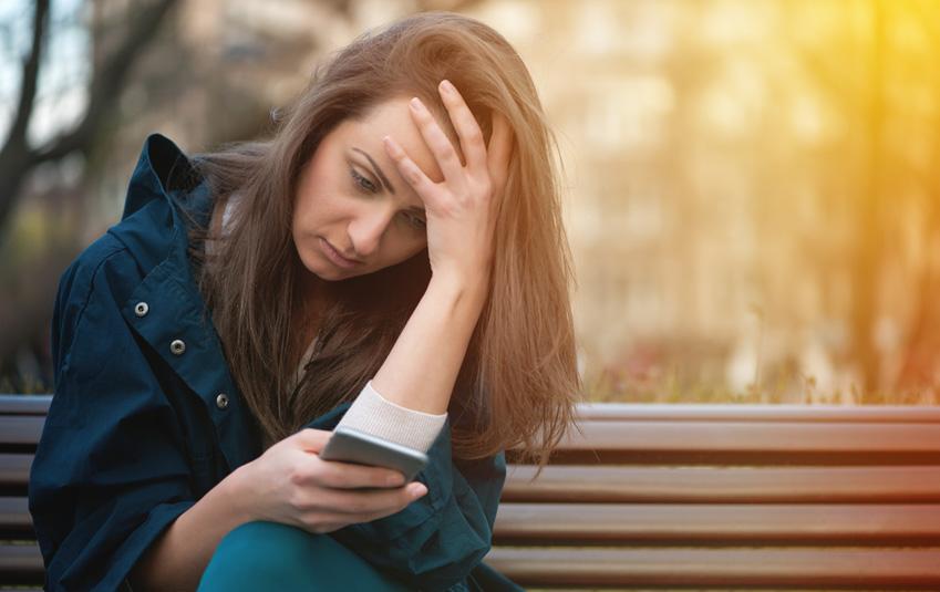 Mujer triste viendo las redes sociales